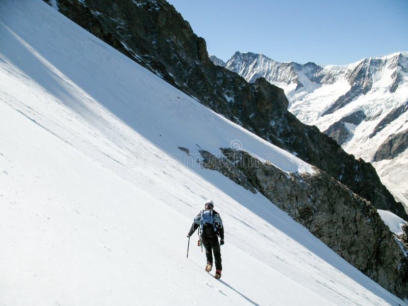 Ορειβάτης βουνών που κάτω από μόνο πέρα από έναν απότομο παγωμένο παγετώνα στις ελβετικές Άλπεις επάνω από Grindelwald στοκ φωτογραφία
