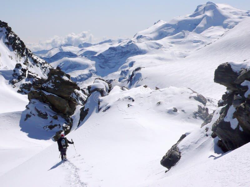 Ορειβάτης βουνών που φέρνει πολύ εξοπλισμό αναρρίχησης στη σειρά βουνών Mischabel στις ελβετικές Άλπεις επάνω από την αμοιβή Saas στοκ εικόνα