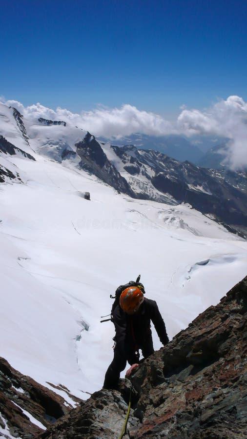 Ορειβάτης βουνών στη σκιαγραφία που αναρριχείται σε μια απότομη δύσκολη αιχμή βουνών υψηλή επάνω από τους άσπρους και άγριους παγ στοκ εικόνα