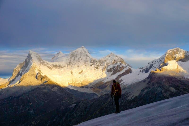 Ορειβάτης βουνών στον παγετώνα Nevado Pisco στην ανατολή με τις τέσσερις αιχμές Nevado Huandoy στο υπόβαθρο στοκ εικόνα με δικαίωμα ελεύθερης χρήσης