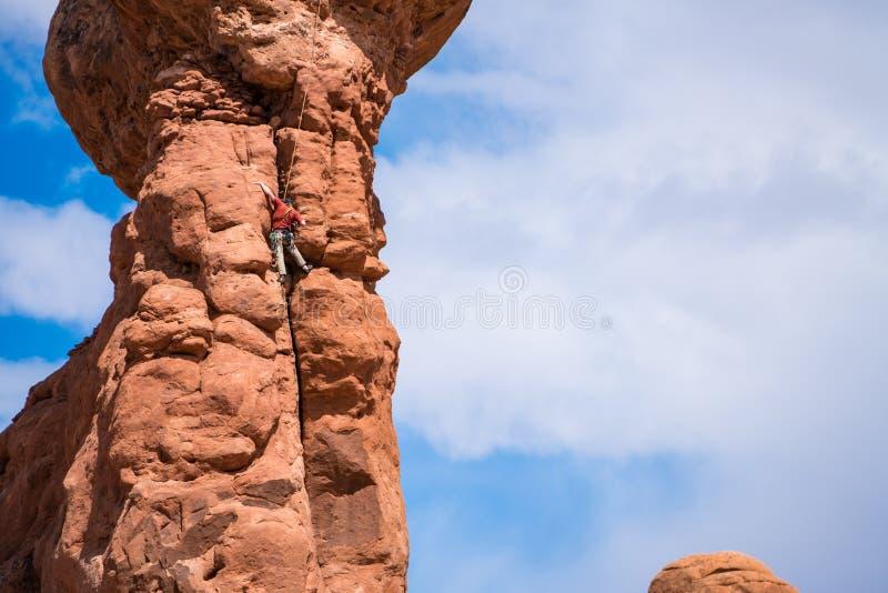 Ορειβάτης βράχου πάνω από ένα hoodoo, Γιούτα στοκ φωτογραφίες