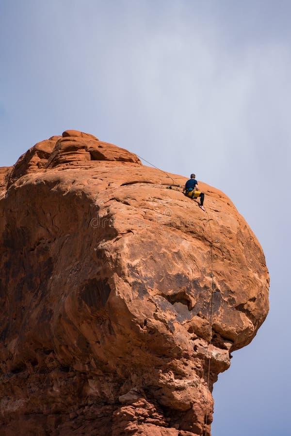 Ορειβάτης βράχου πάνω από ένα hoodoo, Γιούτα στοκ φωτογραφία