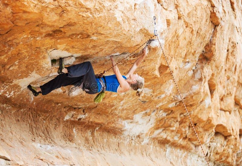 Ορειβάτης βράχου που αγωνίζεται να αποτελέσει την επόμενη μετακίνηση στοκ εικόνες με δικαίωμα ελεύθερης χρήσης