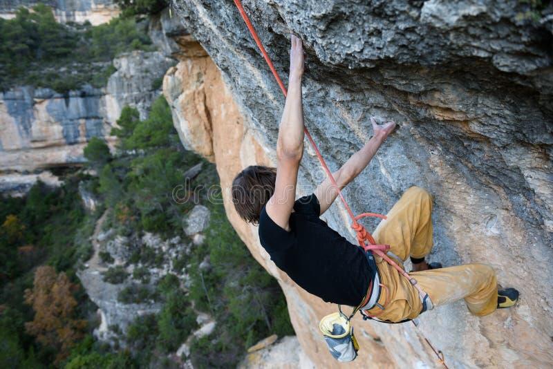 Ορειβάτης βράχου που ανέρχεται έναν απότομο βράχο πρόκλησης Ακραίο αθλητικό climbi στοκ εικόνα με δικαίωμα ελεύθερης χρήσης