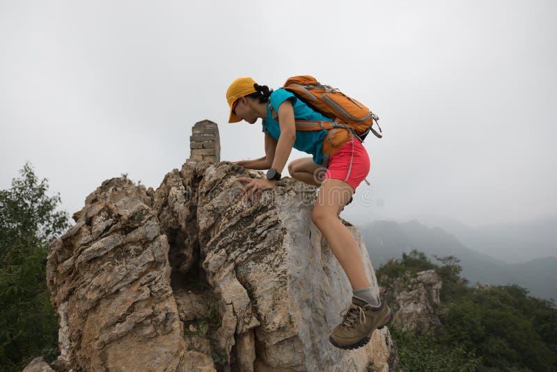 ορειβάτης γυναικών που αναρριχείται στο βράχο στην κορυφή του βουνού στοκ εικόνες