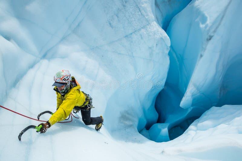 Ορειβάτης πάγου που ανέρχεται επιδέξια από ένα ογκώδες mouin στον παγετώνα Matanuska στοκ φωτογραφίες