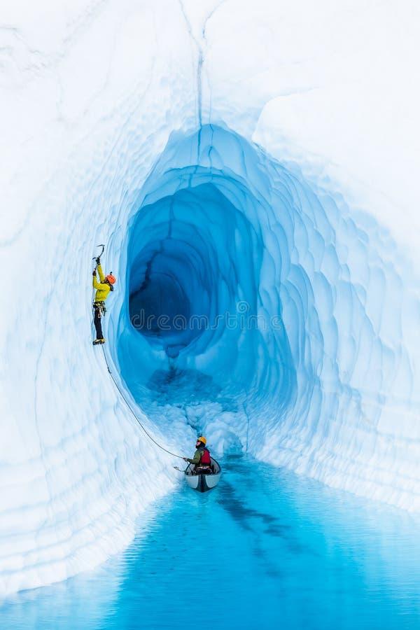 Ορειβάτης πάγου που οδηγεί από ένα διογκώσιμο κανό σε μια μπλε λίμνη μπροστά από μια σπηλιά πάγου στην Αλάσκα στοκ εικόνες