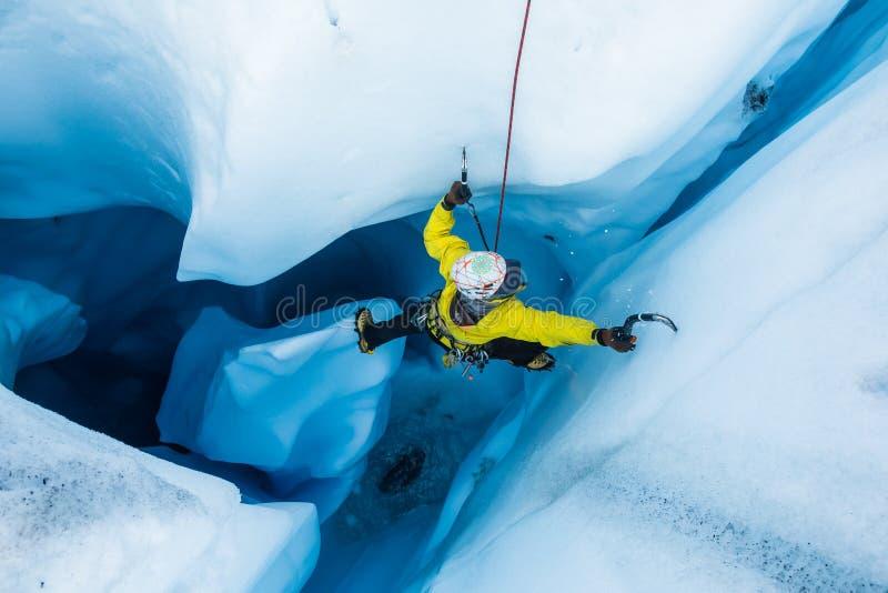 Ορειβάτης πάγου στο piller μέσα στην κάθετη σπηλιά πάγου στον παγετώνα Matanuska στοκ εικόνες