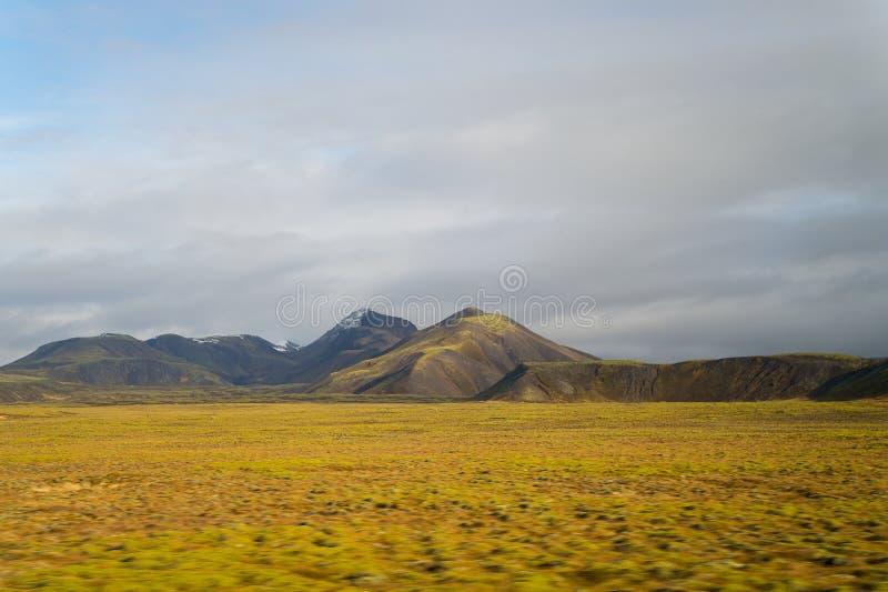 Ορεινή περιοχή στην Ισλανδία Βουνά με το πράσινο βρύο στο νεφελώδη ουρανό στοκ φωτογραφία