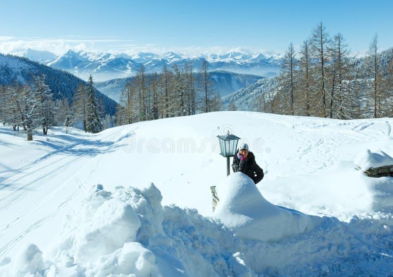 Ορεινός όγκος και γυναίκα βουνών χειμερινού Dachstein κοντά στο λαμπτήρα. στοκ φωτογραφία