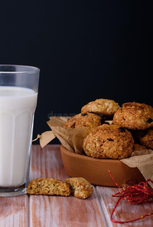 Ορεκτικά και νόστιμα oatmeal μπισκότα με τις σταφίδες και γάλα στο α στοκ φωτογραφία