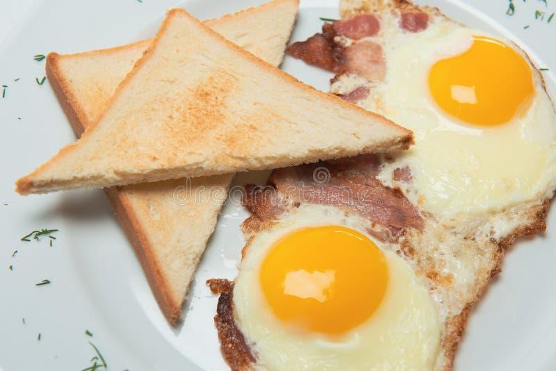 Ορεκτικά τηγανισμένα αυγά στο άσπρο πιάτο με τις φρυγανιές και το μπέϊκον που διακοσμείται με την πρασινάδα στοκ εικόνα με δικαίωμα ελεύθερης χρήσης