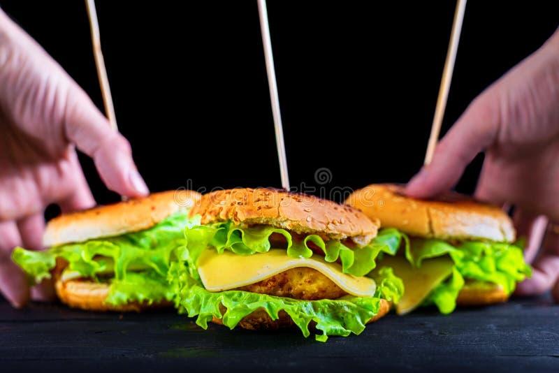 Ορεκτικό και φρέσκο burger σε έναν ξύλινο μαύρο πίνακα, έμβλημα διαφήμισης στοκ φωτογραφίες