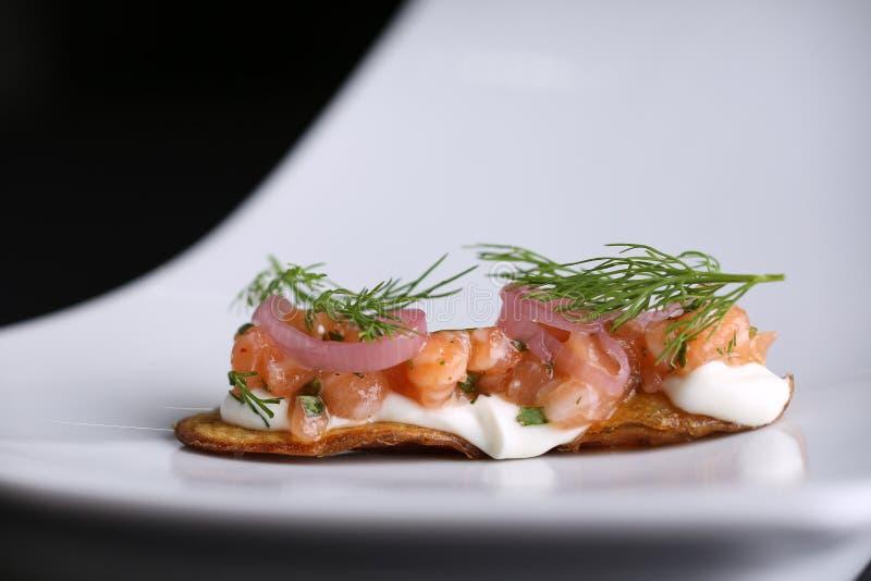 Ορεκτικό στα τηγανισμένα δέρματα πατατών του κόκκινου αλατισμένου σολομού, του τυριού κρέμας, των κρεμμυδιών και του άνηθου στο ά στοκ εικόνες με δικαίωμα ελεύθερης χρήσης