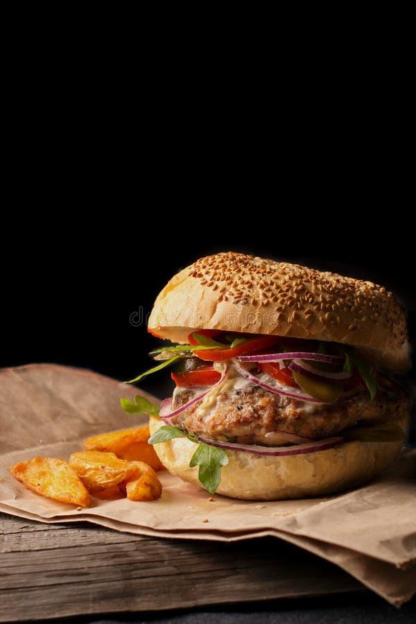 Ορεκτικό χάμπουργκερ με τα μπλε κρεμμύδια, τις ντομάτες και τα πράσινα σε μια ξύλινη σανίδα στοκ φωτογραφίες