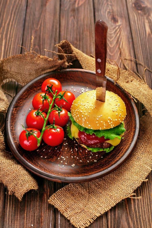 Ορεκτικό burger με τις ντομάτες στον πίνακα στοκ φωτογραφίες