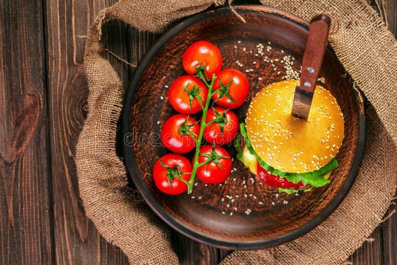 Ορεκτικό burger με τις ντομάτες στον πίνακα στοκ εικόνα