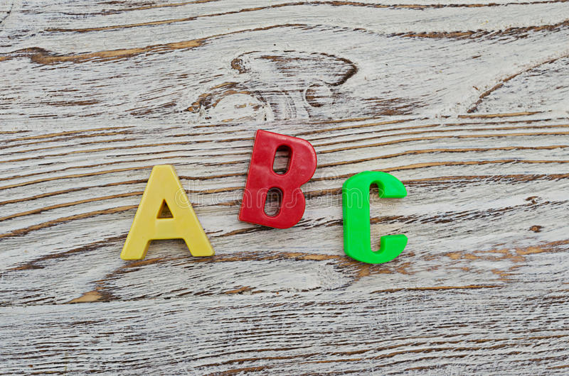 Ορθογραφία ABC των ζωηρόχρωμων πλαστικών επιστολών στο ξύλινο υπόβαθρο στοκ εικόνες