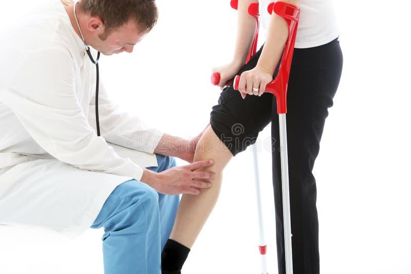 Ορθοπεδικός χειρούργος που εξετάζει το γόνατο της γυναίκας στοκ εικόνα με δικαίωμα ελεύθερης χρήσης