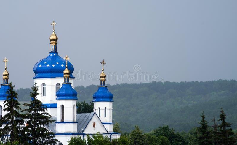 Ορθόδοξη Εκκλησία με τους επιχρυσωμένους θόλους σε έναν λόφο στη μέση του δάσους στοκ φωτογραφίες
