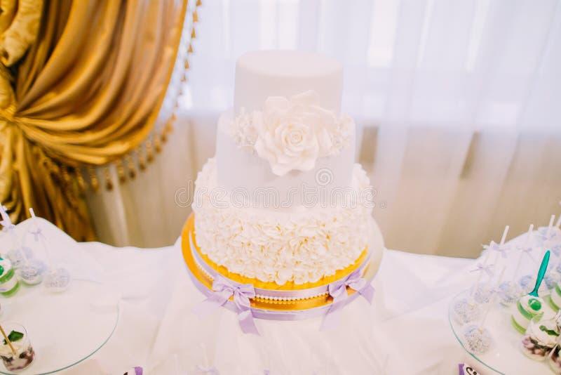 Οριζόντια άποψη του άσπρου γαμήλιου κέικ αμυγδαλωτού που διακοσμείται με τα τριαντάφυλλα στοκ φωτογραφίες