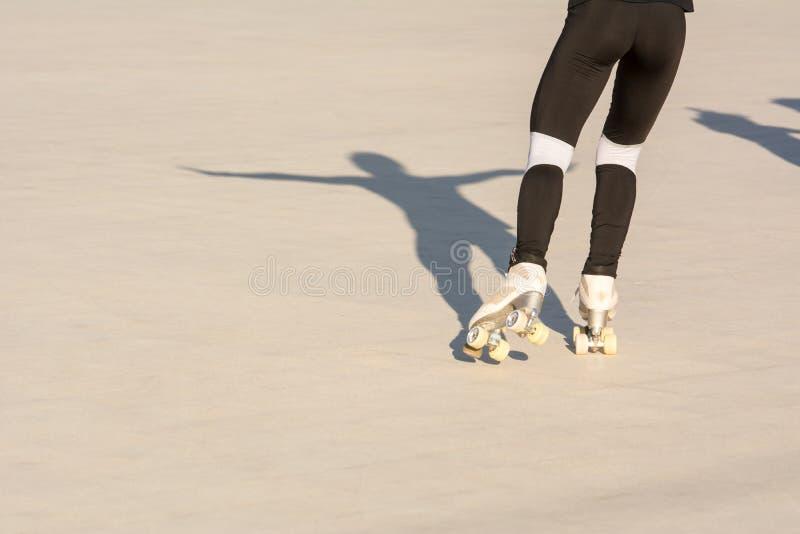 Οριζόντια άποψη OD ένα κορίτσι που κάνει πατινάζ με την ανοικτή σκιά όπλων στοκ εικόνα