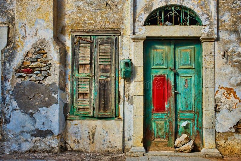 Οριζόντια φωτογραφία αρχαίας πράσινης ξύλινα πόρτας και παράθυρο σε παλιό κίτρινο τοίχο στην Ελλάδα στοκ φωτογραφίες με δικαίωμα ελεύθερης χρήσης