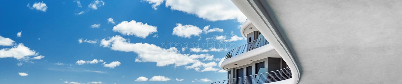 Οριζόντιοι καλλιεργημένοι σύγχρονοι κτήριο και μπλε ουρανός εικόνας στοκ φωτογραφία