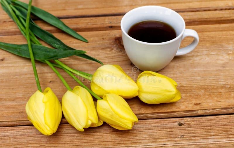 Ορισμένη φωτογραφία αποθεμάτων Θηλυκή σκηνή άνοιξη, floral σύνθεση Δέσμη των όμορφων τουλιπών και του καφέ στον ξύλινο πίνακα στοκ φωτογραφίες με δικαίωμα ελεύθερης χρήσης