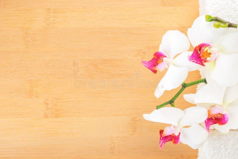 ορχιδέα και άσπρες πετσέτες στο ξύλινο υπόβαθρο μπαμπού στοκ εικόνα