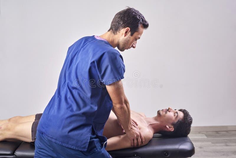 Οστεοπάθεια, έννοια αποκατάστασης αθλητικών τραυματισμών Ένας αρσενικός ασθενής που πάσχει από τον πόνο στην πλάτη και φυσικό Chi στοκ εικόνες