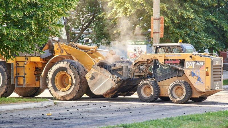 Ουκρανία, Shostka - 14 Ιουνίου 2019: Ένα τρακτέρ χύνει την καυτή άσφαλτο σε άλλο, κατασκευή ενός νέου δρόμου σε μια πόλη στοκ φωτογραφία με δικαίωμα ελεύθερης χρήσης