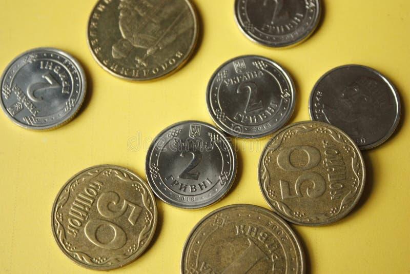 Ουκρανικά νομίσματα που απομονώνονται στο κίτρινο υπόβαθρο Τα νομίσματα κινηματογραφήσεων σε πρώτο πλάνο βρίσκονται στο κέντρο το στοκ εικόνα με δικαίωμα ελεύθερης χρήσης