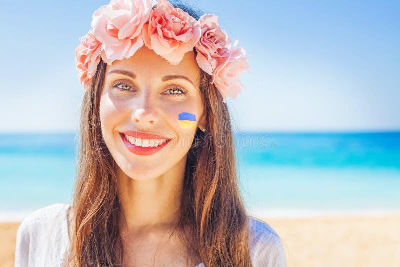 Ουκρανική γυναίκα που φορά το παραδοσιακό στεφάνι με τη σημαία που χρωματίζεται στο μάγουλό της στοκ εικόνα