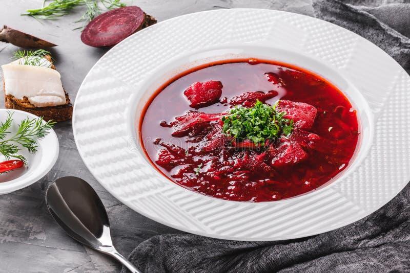 Ουκρανική και ρωσική παραδοσιακή σούπα παντζαριών - borscht στο πιάτο με το καρύκευμα, σκόρδο, πρασινίζει στο αγροτικό υπόβαθρο,  στοκ εικόνα