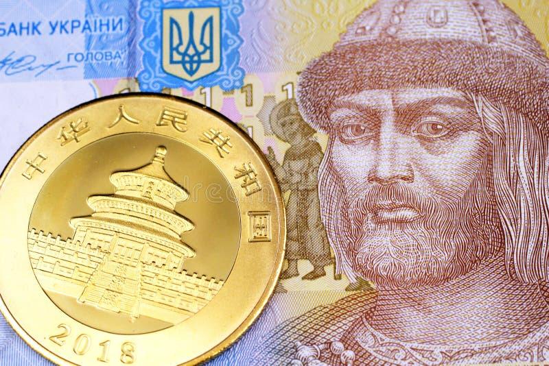 Ουκρανικός τραπεζογραμμάτιο hryvnia με ένα χρυσό κινεζικό νόμισμα ράβδου στοκ εικόνες