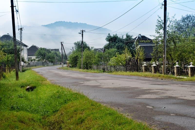 Ουκρανικό χωριό Τοπίο με το δρόμο ασφάλτου Για τα αγροτικά και περιφερειακά θέματα στοκ εικόνα με δικαίωμα ελεύθερης χρήσης