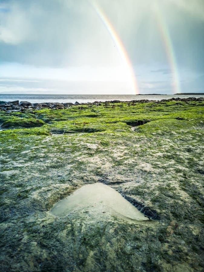 Ουράνιο τόξο επάνω από τα διάσημα ίχνη δεινοσαύρων σε μια παραλία Corran από Staffin στο νησί της Skye στοκ εικόνες