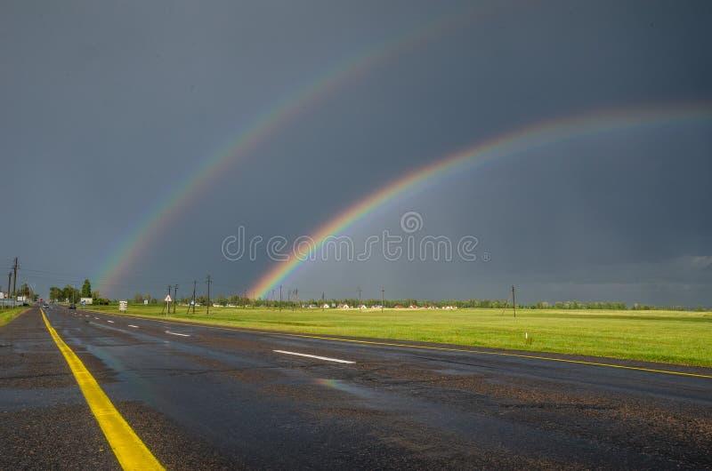 Ουράνιο τόξο μετά από τη βροχή στο δρόμο για το σπίτι στοκ φωτογραφία