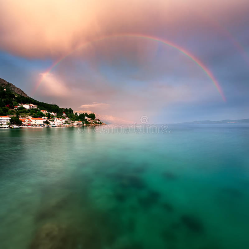 Ουράνιο τόξο πέρα από τη δύσκολη παραλία και μικρό χωριό μετά από τη βροχή στοκ εικόνες