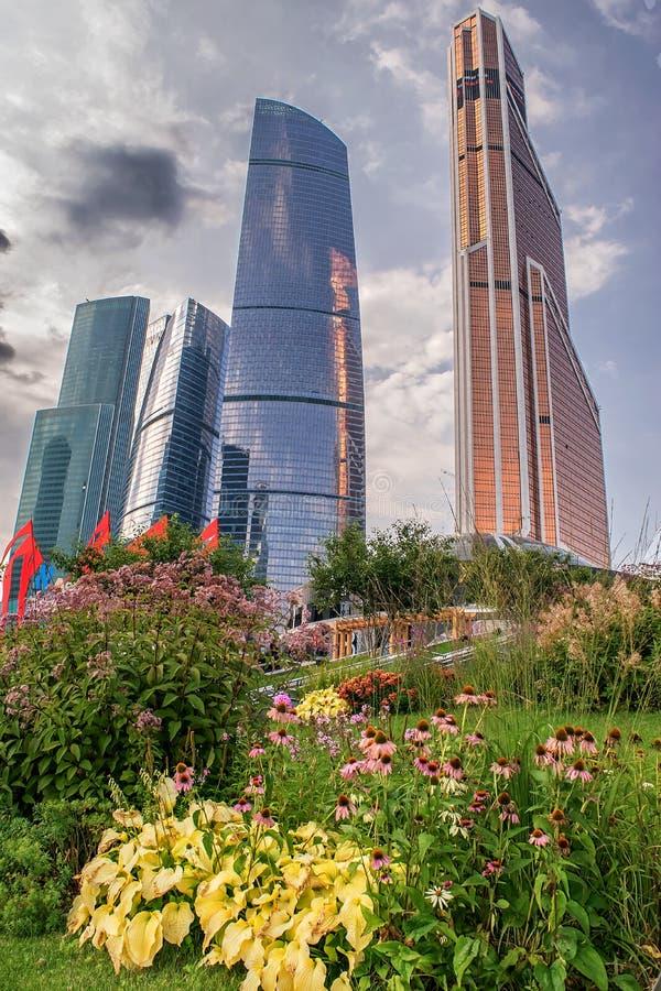 ουρανοξύστες και πολυκατοικίες στο στο κέντρο της πόλης εμπορικό κέντρο σε ένα υπόβαθρο ενός πράσινου πάρκου με τα κρεβάτια λουλο στοκ εικόνες