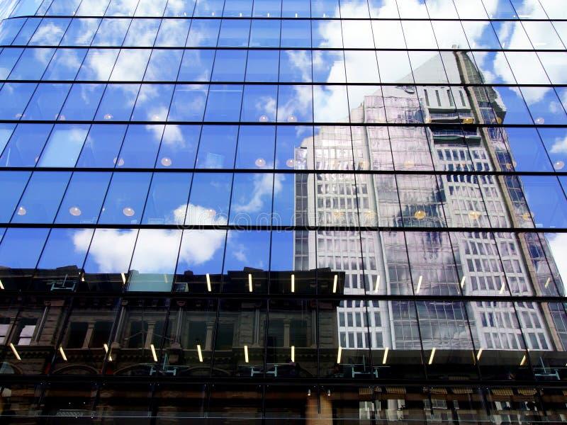 Ουρανοξύστες, μπλε ουρανός και σύννεφα που απεικονίζονται στη βερνικωμένη πρόσοψη οικοδόμησης στοκ εικόνες