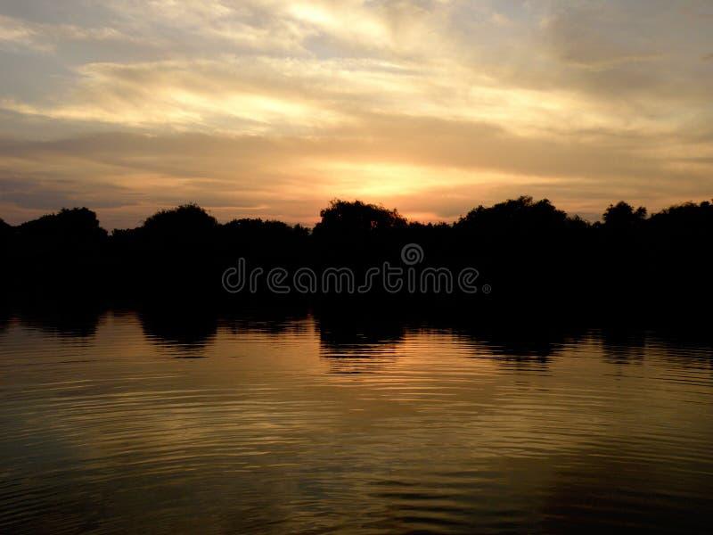 Ουρανός ηλιοβασιλέματος που απεικονίζει στη λίμνη ή τον ποταμό στοκ εικόνες