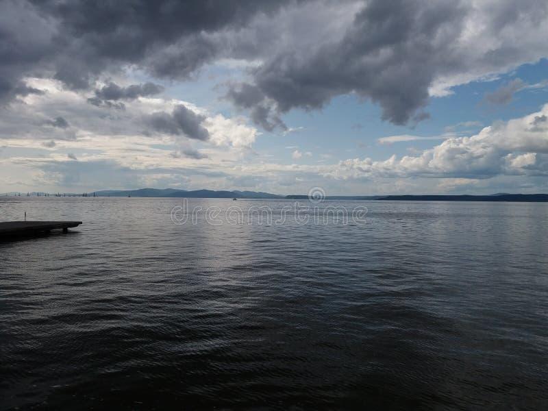 Ουρανός με γκρι σύννεφα και μπλε θάλασσα στοκ φωτογραφία