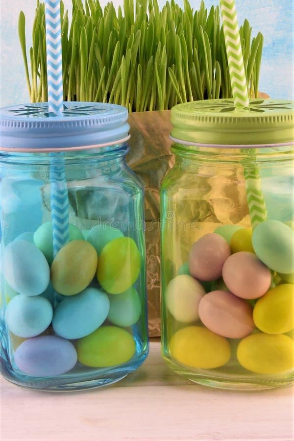 Ουρανός-μπλε και πράσινα διαφανή βάζα γυαλιού με τα χρωματισμένα αυγά Πάσχας και την πράσινη χλόη στοκ εικόνα
