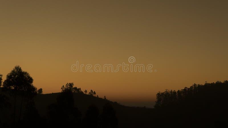 Ουρανός σούρουπου ξημερωμάτων αμέσως πριν από την ανατολή με τη σκιαγραφία των δέντρων και του μικρού λόφου στο πρώτο πλάνο στοκ εικόνα