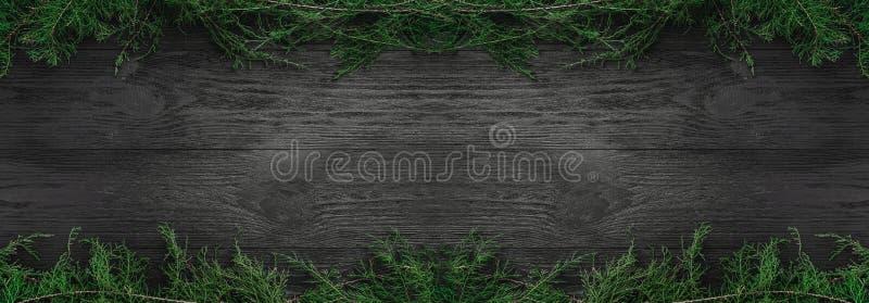 ουρανός santa του Klaus παγετού Χριστουγέννων καρτών τσαντών Μαύρο ξύλινο υπόβαθρο με τους κλάδους έλατου πάνω-κάτω, τοπ άποψη Συ στοκ φωτογραφίες