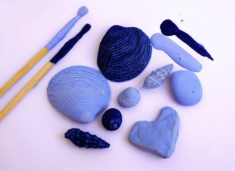 Ουσία, κοχύλια και πέτρες θάλασσας που χρωματίζονται με τη βούρτσα στο μπλε χρώμα διαστημικές διακοπές θερινών κειμένων μνημών ει στοκ εικόνες