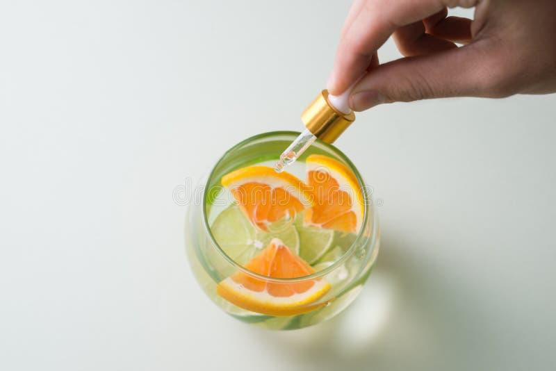 Ουσιαστικό πετρέλαιο με το πορτοκάλι - βιταμίνη C Φυσικές θεραπείες, βιταμίνη C πτώσης - dropper στοκ εικόνα