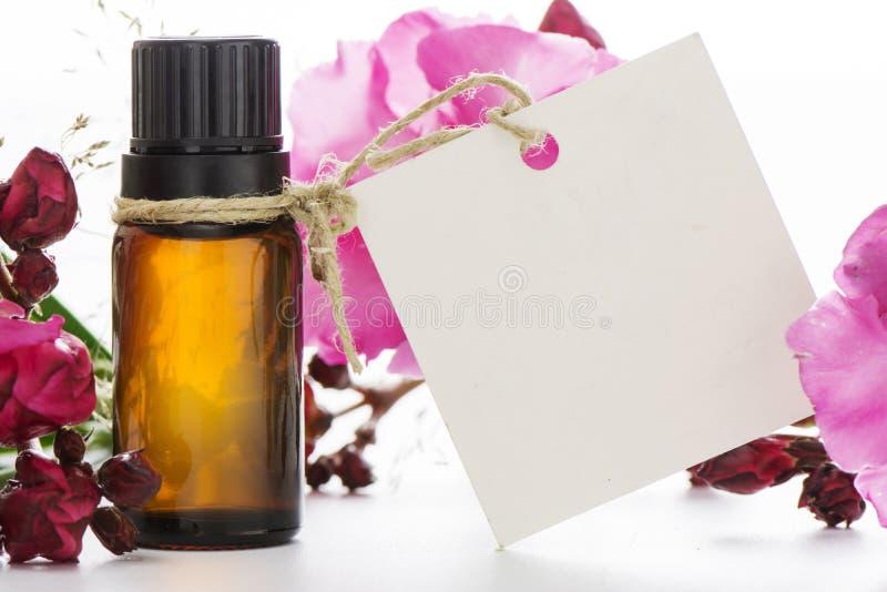 Ουσιαστικό πετρέλαιο, κενά ετικέττες και λουλούδια τριαντάφυλλων στοκ εικόνες